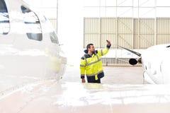 Flygplatsarbetare kontrollerar ett flygplan för säkerhet i en hangar Fotografering för Bildbyråer
