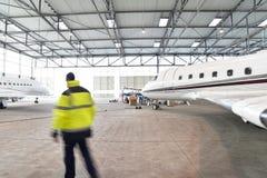 Flygplatsarbetare kontrollerar ett flygplan för säkerhet i en hangar Arkivfoto