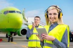 Flygplatsarbetare med flygplanet på bakgrunden Royaltyfria Bilder