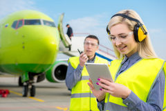 Flygplatsarbetare med flygplanet på bakgrunden Royaltyfri Foto