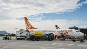 Flygplatsarbetare på Rio de Janeiro ` s Santos Dumont Airport bär ut arbetsuppgifter på ett Gol trafikflygplanflygplan Royaltyfri Bild