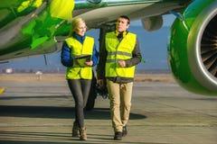 Flygplatsarbetare som behandlar flygplanet Arkivbild