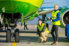Flygplatsarbetare som behandlar flygplanet Arkivfoton