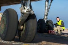 Flygplatsarbetare som kontrollerar chassiet Arkivfoton