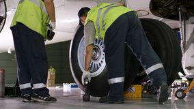 Flygplatsarbetare som kontrollerar chassiet Motor och chassi av passagerareflygplanet under tungt underhåll Teknikerkontroller Royaltyfri Fotografi