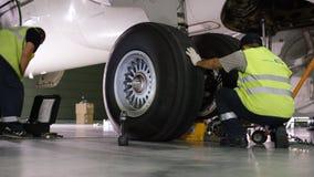 Flygplatsarbetare som kontrollerar chassiet Motor och chassi av passagerareflygplanet under tungt underhåll Teknikerkontroller Arkivbilder