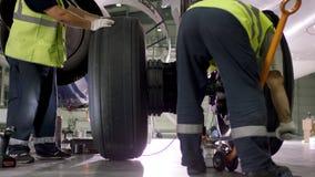 Flygplatsarbetare som kontrollerar chassiet Motor och chassi av passagerareflygplanet under tungt underhåll Teknikerkontroller Arkivfoton