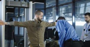 Flygplatsarbetare som kontrollerar passageraren med metalldetektorn stock video