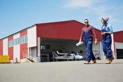 Flygplatsarbetare som lämnar den plana hangaren Arkivbild
