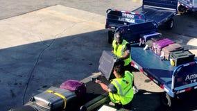 Flygplatsarbetare som laddar bagage till flygplanet stock video