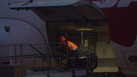 Flygplatsarbetare som lastar av flygplan på natten stock video