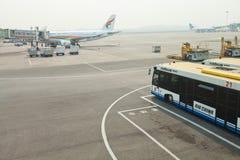 Flygplatsbuss bredvid landgång och flygplanet Arkivfoton
