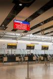 Flygplatsen kontrollerar in skrivbord- och egentecknet Royaltyfria Bilder