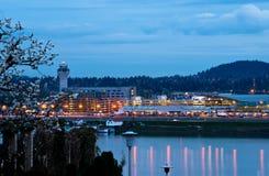 Flygplatsen tänder med reflexion i floden på vårafton Arkivbilder