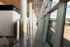 Flygplatskorridor längs den genomskinliga glasväggen med fönstret Arkivfoton