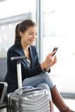 Flygplatskvinna på den smarta telefonen på porten - flygresa Fotografering för Bildbyråer