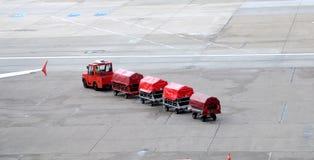 Flygplatslastbilar som behandlar bagage Fotografering för Bildbyråer