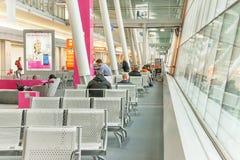 Flygplatspassagerare väntar i terminalen för deras flyg Royaltyfri Fotografi