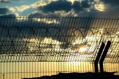 Flygplatssäkerhetsstaket över materielfotoet för molnig himmel Arkivfoto