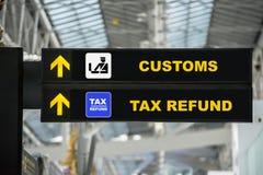 Flygplatsskatteåterbäringen och egenar undertecknar in terminalen på flygplatsen fotografering för bildbyråer