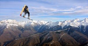Flygsnowboarder på berg Fotografering för Bildbyråer