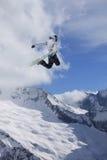 Flygsnowboarder på berg extrem sport Arkivbild