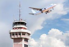 Flygtrafikkontrolltorn i internationell flygplats med passagerareflygplanstrålen som tar av royaltyfri fotografi