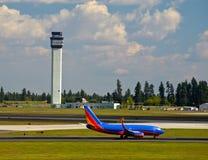 Flygtrafikkontrolltorn och ett flygplan Royaltyfri Fotografi