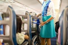Flygvärdinnaportiondrinkar till passagerare ombord arkivbilder