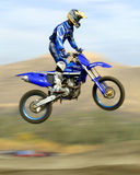 Flyin' high. Motocross racer catchin'air Stock Image