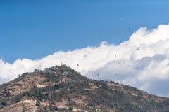 Flyinf de muitos paragliders sobre a montanha Sarangkot Imagens de Stock Royalty Free