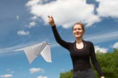 Flying. Paper plane in the foreground and the nice girl on a background of the beautiful blue sky with clouds Royalty Free Stock Photos