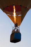 Flying. Two pilots in a basket of a flying balloon with working torch Stock Photography