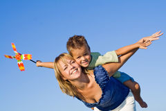 We are flying. Woman and littel boy playing aeroplane with a pinwheel against blue summer sky Stock Photos