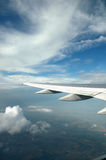 Flying. View of an airplane wing against a sunny blue sky with wispy clouds. The view also incluedes the ground below. Flying the friendly skies Stock Images