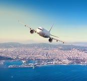 Flying above Barcelona city. Commercial airplane flying above Barcelona city, in beautiful sunset light stock image