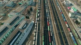 Flying above cargo train moving past. Train station view from the top. Aerial video shows large train depot with many trains stock footage