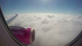 Flying above clouds, airplane wing turbine, passenger porthole stock footage