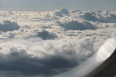 Flying above the clouds in daytime. Airplane travel Royalty Free Stock Photos