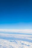 Flying above the clouds view  from a airplane porthole Royalty Free Stock Images