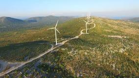 Flying above elegant ecological wind turbines on green hills. Flying above elegant ecological wind turbines on green sunlit hills stock video footage