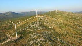 Flying above elegant ecological wind turbines on green hills. Flying above elegant ecological wind turbines on green sunny hills stock video