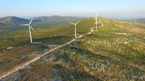 Flying above elegant ecological wind turbines on green hills. Flying above elegant ecological wind turbines on green sunny hills stock video footage