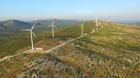 Flying above elegant ecological wind turbines on green hills. Flying above elegant ecological wind turbines on green sunny hills stock footage