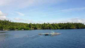 Fly above fisherman´s catamaran in Lembeh Strait. Flying above fisherman´s boat catamaran by tropical island with green palm tree forest in Lembeh Strait stock video