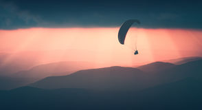 Flying above the foggy hills. Instagram stylisation. Paraglide silhouette flying over the mountains. Beautiful rays of sunset light on a foggy hills of mountain Royalty Free Stock Photos