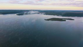 Flying above foggy lake early in the morning stock footage
