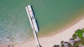 Flying above the pier, over a reef and blue ocean Aerial view of beautiful beach stock video
