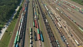 Flying above railroad freight trains. Railroads and export container trains. On industrial railway terminal. Aerial view. Industrial railway. Logistics concept stock video
