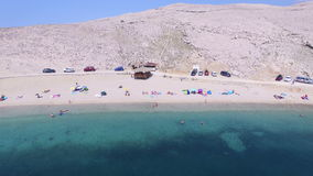 Flying above tourists on quiet family beach on Pag island, Croatia stock video footage